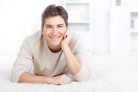 floor covering: Young smiling man on the carpet at home