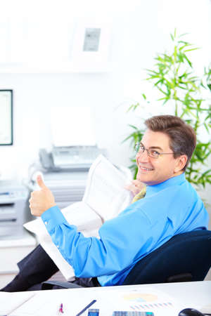 Smiling businessman reading a newspaper in the office  photo