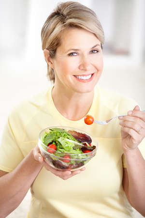 Mature smiling woman  with fruits and vegetables.