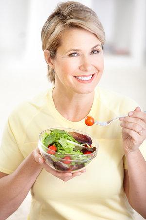 Volwassen lachende vrouw met vruchten en groenten.   Stockfoto