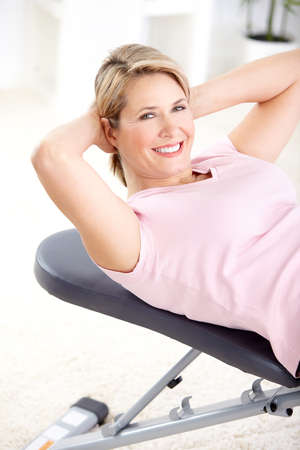 exercitation: Gym & Fitness. Smiling elderly woman working out.