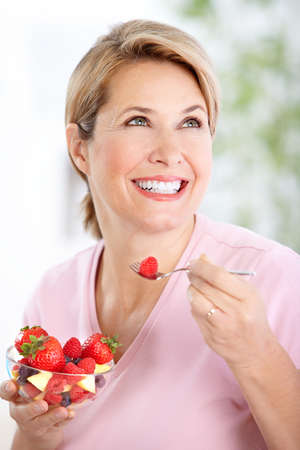Mature smiling woman  eating strawberries  photo