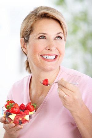 Mature smiling woman  eating strawberries Stock Photo - 8255792