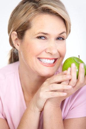 Mature smiling woman with apple  Banco de Imagens