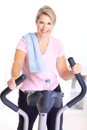 svelte: Gym & Fitness. Smiling elderly woman working out.