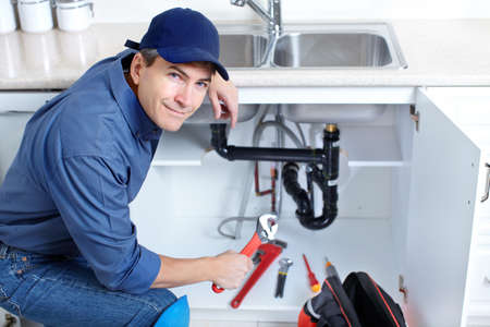 plumbing: Mature plumber fixing a sink at kitchen   Stock Photo