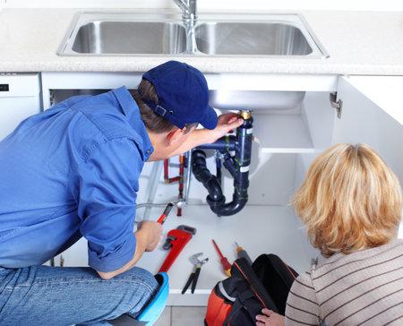 成熟した鉛管工のキッチン シンクを固定します。 写真素材