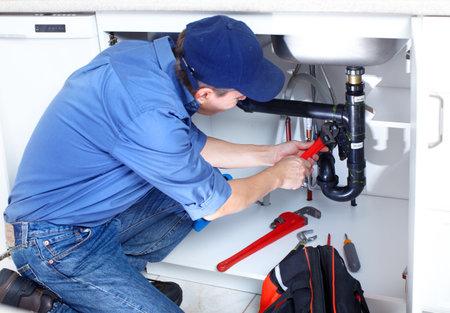 outils plomberie: Plombier mature fixant un �vier de cuisine
