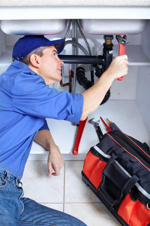 repairman: Mature plumber fixing a sink at kitchen   Stock Photo