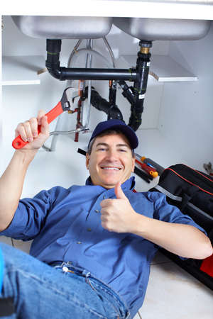 Mature plumber fixing a sink at kitchen Stock Photo - 8255802