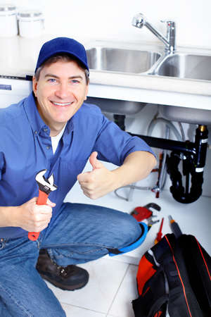 Mature plumber fixing a sink at kitchen Stock Photo - 8255778