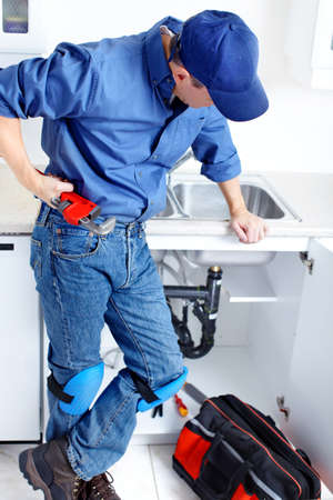 Mature plumber fixing a sink at kitchen Stock Photo - 8255822
