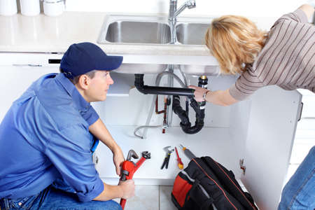 Mature plumber fixing a sink at kitchen  photo