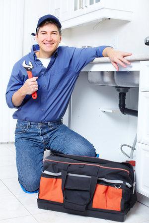 Mature plumber fixing a sink at kitchen Reklamní fotografie - 8255694