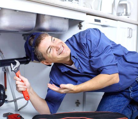 Mature plumber fixing a sink at kitchen  Banco de Imagens