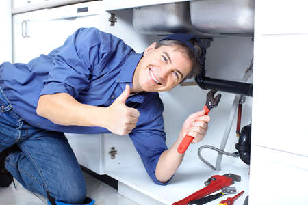 Mature plumber fixing a sink at kitchen  Stock Photo