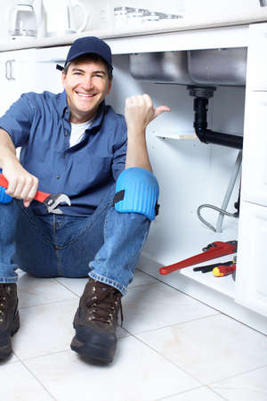 Mature plumber fixing a sink at kitchen Stock Photo - 8255789