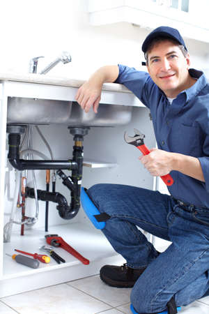 sink: Mature plumber fixing a sink at kitchen  Stock Photo