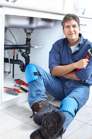 plumber tools: Mature plumber fixing a sink at kitchen  Stock Photo