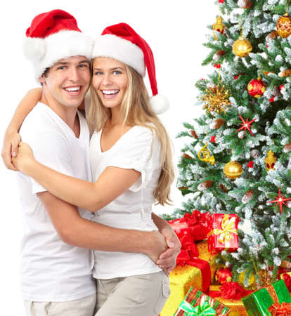 Young happy couple near  a Christmas tree. Isolated over white background Stock Photo - 8255844