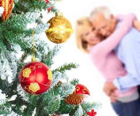 Oudere gelukkige paar in de buurt van een kerst boom. Geïsoleerd op witte achtergrond  Stockfoto