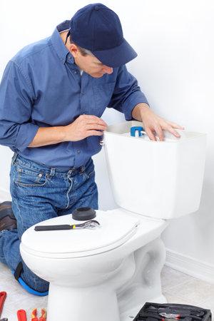 toilet: Mature plumber near a flush toilet
