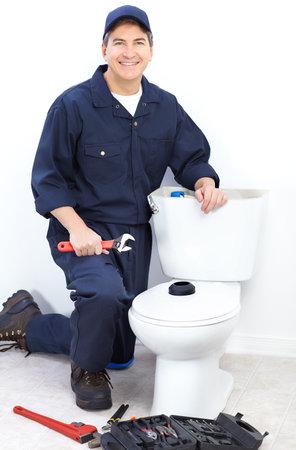 Mature plumber near a flush toilet