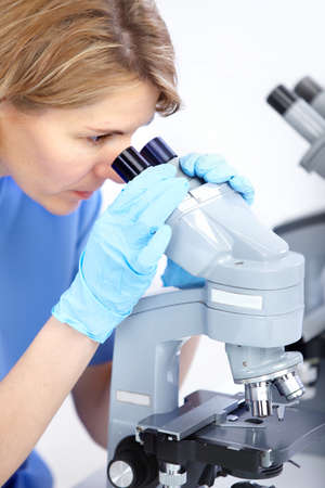 Woman working with a microscope in a lab Stock Photo - 8255872