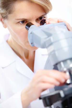 Woman working with a microscope in a lab