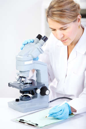 Woman working with a microscope in a lab Фото со стока