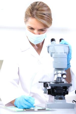 microscopio: Mujer que trabaja con un microscopio en un laboratorio