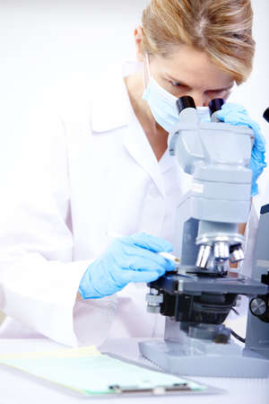 Woman working with a microscope in a lab 스톡 콘텐츠