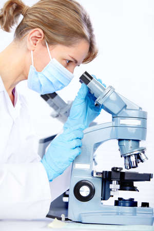 Woman working with a microscope in a lab  Stock Photo