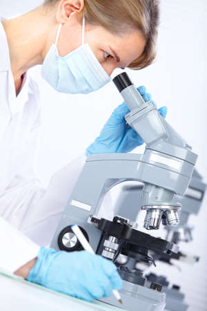 Woman working with a microscope in a lab  版權商用圖片