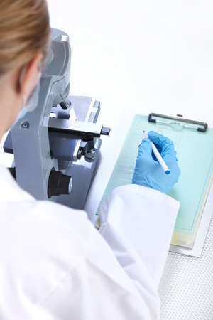 Woman working with a microscope in a lab Stock Photo - 8255852