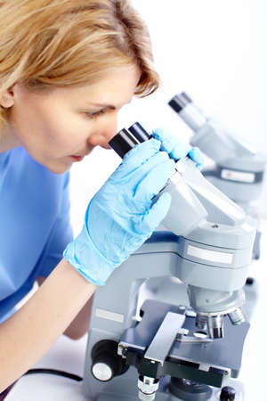 medical laboratory: Woman working with a microscope in a lab  Stock Photo