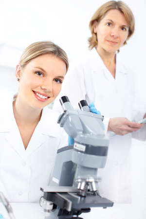 laboratorian: Women working with a microscope in a lab  Stock Photo