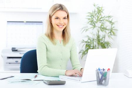sexy secretary: Joven sonriente mujer de negocios que trabajan con port�til  Foto de archivo