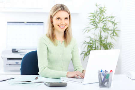 sexy secretary: Young smiling  business woman working with laptop