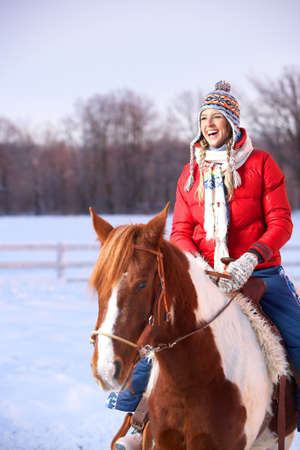 Young  happy smiling woman with horse. Winter sport  photo
