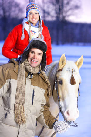 Young  happy smiling couple with horse. Winter sport  photo