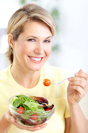 seniors homes: Mature smiling woman  eating salad,  fruits and vegetables.   Stock Photo