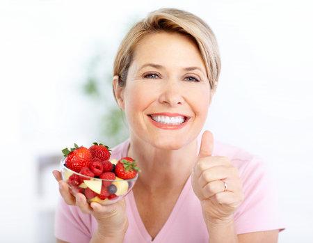 euforia: Mujer sonriente madura comer fresas