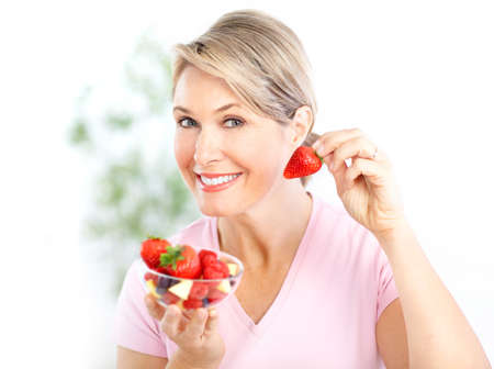 Mature smiling woman  eating strawberries
