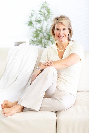 Lachende gelukkige vrouw zittend op de bank thuis