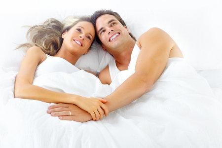 Joven feliz pareja en la cama Foto de archivo - 8512212