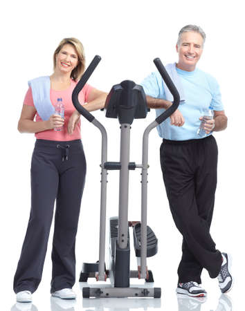 Gym & Fitness. Smiling elderly couple working out. Isolated over white background Stock Photo - 8538329