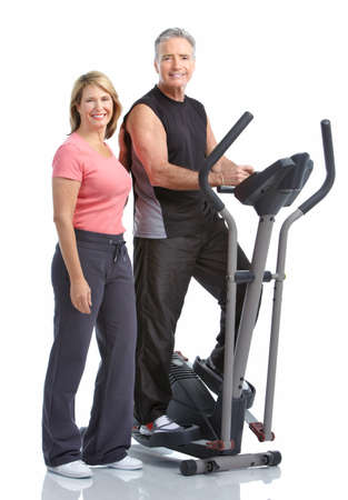 Gym & Fitness. Smiling elderly couple working out. Isolated over white background Stock Photo - 8538385