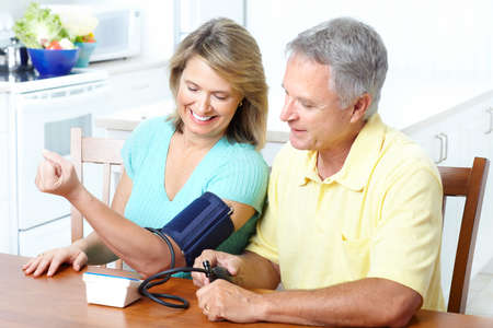 home health care: Seniors couple at home measuring blood pressure. Home monitoring  Stock Photo