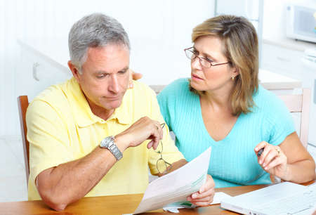 Senior couple reading the bills  Stock fotó
